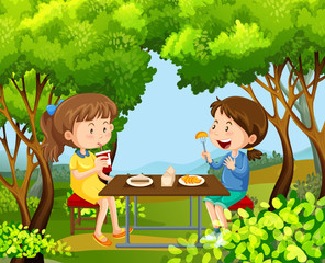 Two girls having picnic in the woods