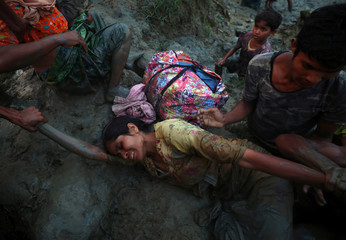 A Rohingya refugee woman is helped out of Naf River as they cross the Myanmar-Bangladesh border in Palong Khali, near Cox's Bazar