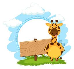 Giraffe standing next to blank wooden sign