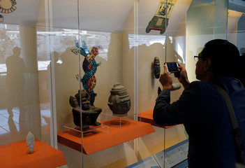 A woman takes pictures with her cellphone during an opening exhibition of artefacts discovered over the last 40 years at archaeology museum, during a media tour at the Templo Mayor Aztec complex in Mexico City