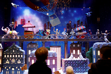 People look at a Christmas holiday window display outside the Galeries Lafayette department store in Paris