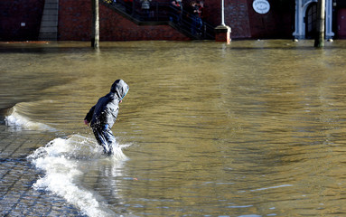 """A child plays in the water at the Fish Market flooded during stormy weather caused by a storm called """"Herwart,"""" in Hamburg"""