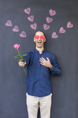 Single adult white man with heart shaped eyes wearing a blue shirt and standing in front of a blackboard with painted hearts holding a rose. Concept of crazy love