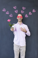 Single adult white man with heart shaped eyes wearing a pink shirt and standing in front of a blackboard with painted hearts holding a rose. Concept of crazy love