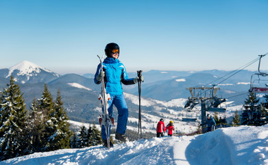 Full length shot of a woman skier in winter sportswear standing on top of a mountain with her skis at winter ski resort. Blue sky, mountains, forests, ski lift and people on the blurred background