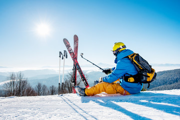 Rearview shot of a skier sitting on the snow on top of the mountain taking selfies with his action camera on a monopod while resting after skiing. Blue sky with sun and winter forest on the background