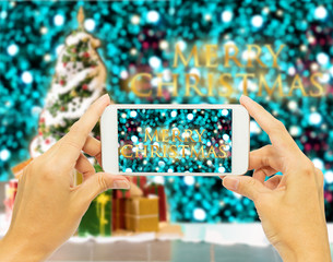 "Hand holding smart phone for take photo ""Merry Christmas """