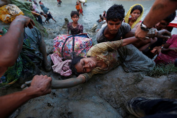 Photographers help a Rohingya refugee woman to come out of Naf river as Rohingya refugees cross the Bangladesh-Myanmar border in Palong Khali