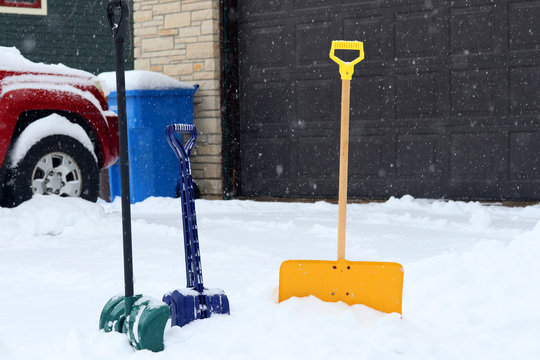 Beautiful winter background. Three colorful shovels in snowdrift on a foreground along covered by fresh snow driveway and garage door on a snowy background.