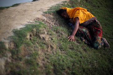 An exhausted Rohingya refugee lies on the ground as she tries to continue her way after crossing from Myanmar into Palang Khali, near Cox's Bazar