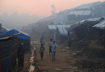 Rohingya refugees walk through Balukhali refugee camp at sunrise near Cox's Bazar