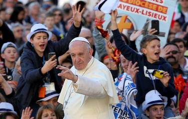 Pope Francis waves as he arrives during his Wednesday general audience in Saint Peter's square at the Vatican