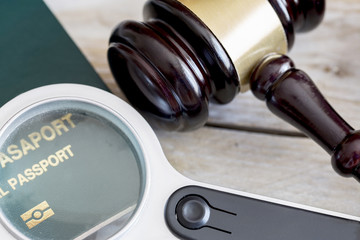 Immigration law concept. Gavel, passport and magnifying glass on wooden table