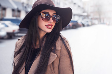 Outdoor fashion portrait of a young beautiful fashionable woman wearing stylish accessories.vintage sunglasses. Female fashion, beauty and advertisement concept. Close up. Copy space for text