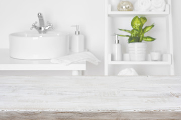Wooden table in front of blurred white bathroom shelves background