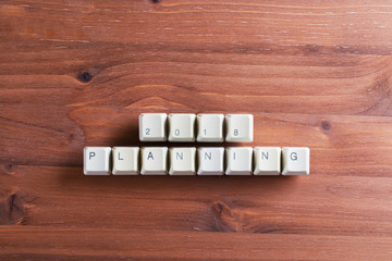 Planning 2018 new year on computer keyboard keys buttons on wooden background