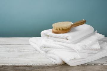 White towels and bath brush on wood over blue background