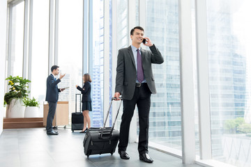 Businessman with baggage calling on mobile phone  at office building hallway