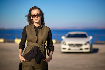 beautiful business woman in sunglasses and business suit at sunset on the background of an expensive car