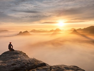 Tourist sit on peak of sandstone rock and watching into colorful mist and fog in  morning valley. Sad man