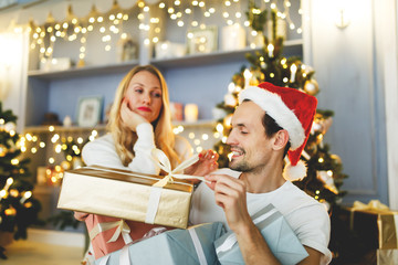 Photo of cheerful man and woman in santa cap with gift in box