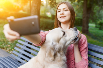 Photo of woman on bench doing selfie with retriever