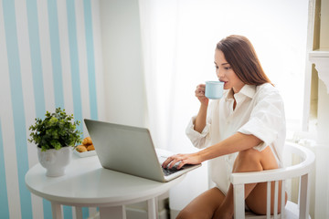 Young beautiful woman using laptop and drinking