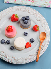 Small round berry cheesecakes on plate and blue background