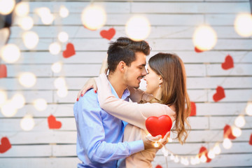 Young couple on Valentine's Day. A loving couple hugs against a background of glowing garlands.