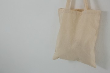 Beige bag hanging against white wall