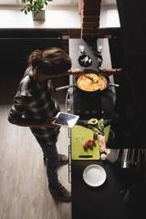 Man using digital tablet while preparing scrambled egg
