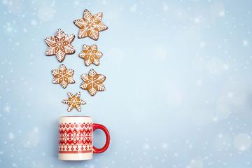 Snowfall from gingerbread snowflakes in Christmas mug on blue background. Copy space.