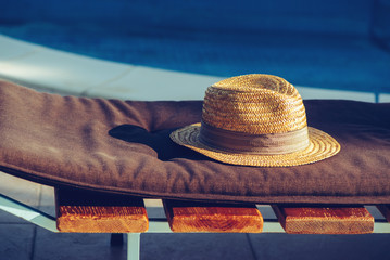 Straw hat on deck chair by the swimming pool