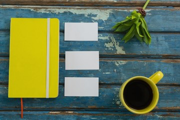 Blank visiting cards, diary, flora and black coffee on wooden