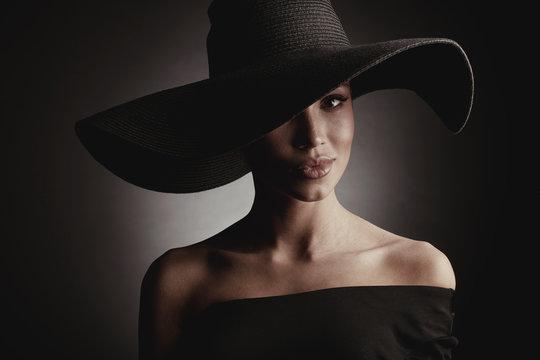 Dark studio portrait of elegant sexy woman in black wide hat and black dress.