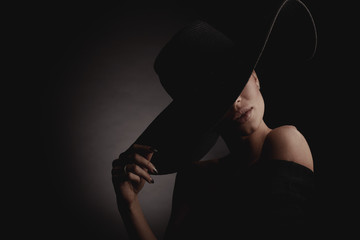 Dramatic dark studio portrait of elegant woman in black wide hat and black dress. Hidden eyes.