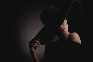 Dramatic dark studio portrait of elegant woman in black wide hat and black dress. Hidden eyes. Wall mural