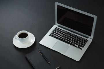 Black coffee, pen, organizer and laptop on black background