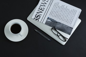 Black coffee, spectacles, pen, laptop and newspaper on black