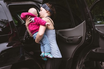 Mother holding her baby near car