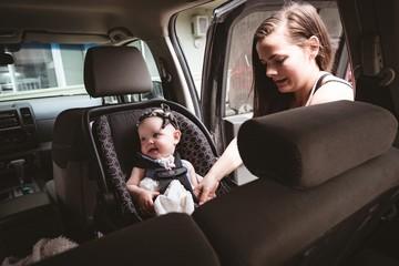 Mother adjusting stroller belt for her baby