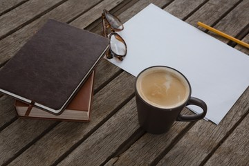 Organizer, coffee, spectacles, pencil and paper on wooden plank