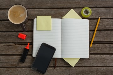 Organizer, coffee, mobile phone and stationery on wooden plank