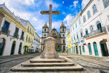 Bright view of the historic tourist district of Pelourinho in Salvador, Brazil, dominated by the large colonial Saint Francis Christian stone cross in the Anchieta Plaza