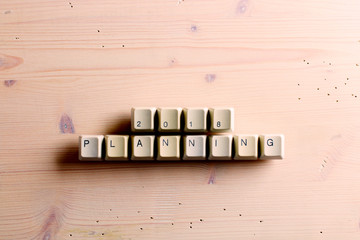 Planning 2018 new year on computer keyboard keys buttons on a wooden background