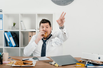overweight businessman eating hamburgers and french fries in office