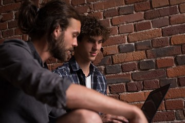 Male executives discussing over laptop