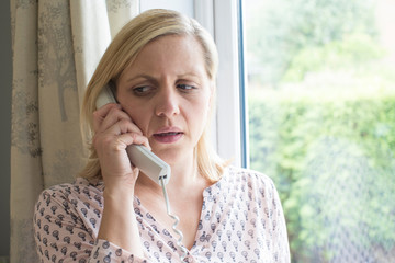 Worried Woman Answering Telephone At Home