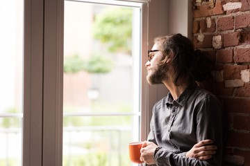 Man looking through window while having coffee