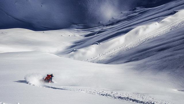 Freeride skier charging through powder snow